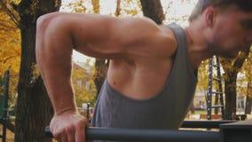 L'atleta viene su e comincia fare un esercizio sulle parallele simmetriche stock footage