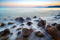 L'atmosphère romantique dans le matin paisible en mer Grands rochers collant de l'horizon onduleux doux de rose de mer avec du pr photos libres de droits