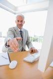 L'atteinte heureuse d'homme d'affaires distribuent pour la poignée de main Photo stock