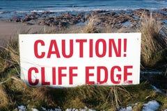 L'attention rouge se connectent le bord glissant de falaise photographie stock