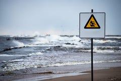 L'attenzione firma vicino al mare con tempo tempestoso Immagine Stock