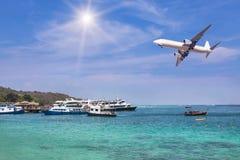 L'atterraggio di aeroplano del passeggero sopra il mare tropicale con le navi giranti e le barche ha attraccato in baia Fotografia Stock