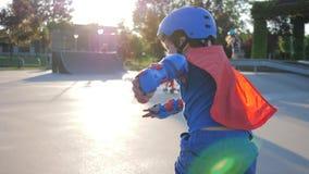 L'attività di sport, bambino impavido in costume del supereroe guida sui rulli e le mani d'ondeggiamento al pattino parcheggiano
