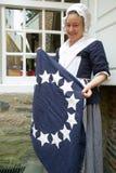 L'attore del Betsy Ross tiene la bandierina coloniale Fotografia Stock
