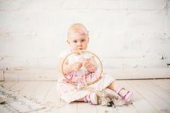 L'attrapeur rêveur d'amulette et le petit bébé un an avec des yeux bleus, blonde s'assied sur le plancher dans une robe et juge photographie stock libre de droits
