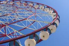 L'attrazione di una ruota panoramica con le cabine rosse e blu in un parco di divertimenti del ` s dei bambini nella città su un  fotografia stock