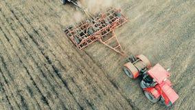 L'attrezzatura arabile coltiva la terra su un vasto campo, vista superiore stock footage