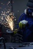 L'attrezzatura d'uso della protezione del lavoratore facendo uso di una smerigliatrice di angolo su metallo e sulla fabbricazione Fotografia Stock