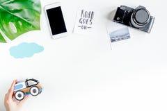 L'attrezzatura di turismo dei bambini con la macchina fotografica ed il cellulare sul piano bianco del fondo pongono il modello Fotografia Stock