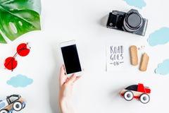 L'attrezzatura di turismo dei bambini con la macchina fotografica ed il cellulare sul piano bianco del fondo pongono il modello Fotografia Stock Libera da Diritti