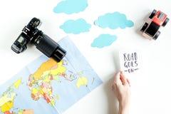 L'attrezzatura di turismo dei bambini con la mappa e la macchina fotografica sul piano bianco del fondo pongono il modello Fotografia Stock
