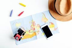 L'attrezzatura di turismo dei bambini con la mappa ed il telefono sul piano bianco del fondo pongono il modello Fotografia Stock