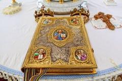 L'attributo della chiesa una bibbia dorata con un fissare l'altare, il vangelo, santo, oro incorona per le spose con gli incroci Fotografie Stock