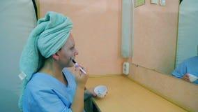 L'attrice nello spogliatoio alla tavola davanti allo specchio mette una maschera sul suo fronte con una spazzola profilo archivi video