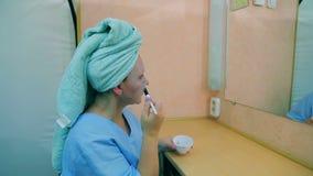 L'attrice nello spogliatoio alla tavola davanti allo specchio mette una maschera sul suo fronte con una spazzola profilo video d archivio