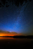 L'aube de matin sur un ciel étoilé de fond s'est reflétée dans l'eau Images libres de droits