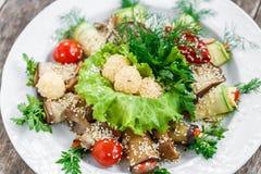 L'aubergine grillée roule et la courgette roule avec des tomates, des champignons, des herbes, des boules de fromage et le sésame Image stock