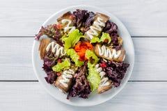 L'aubergine roule avec du fromage, la salade d'ail et de sauce blanche et de laitue part sur le plat blanc et la table en bois Vu Photo stock