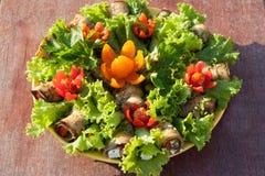 L'aubergine roule et les feuilles de laitue décorées des fleurs coupent des tomates-cerises sur la vue supérieure de fond en bois Image libre de droits