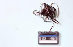L'audio nastro a cassetta con sottratto fuori lega sopra il bordo di legno strutturato blu Immagini Stock Libere da Diritti