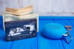 L'audiocassetta con la pila di dollari e il bluetooth portatile parlano immagine stock