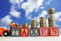 L'augmentation impose le concept avec le chariot élévateur orange poussant le mot d'impôts des cubes en bois avec les piles crois Image stock