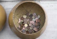 L'aumône d'or roule avec de petites pièces de monnaie thaïlandaises dans le temple bouddhiste image stock