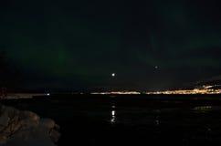 L'aurora borealis che ballano sopra la montagna nevosa ed il fiordo abbelliscono con la luna piena Fotografie Stock Libere da Diritti