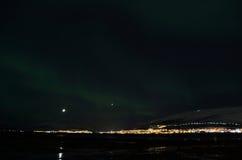 L'aurora borealis dansant au-dessus de la montagne neigeuse et le fjord aménagent en parc avec la pleine lune Photographie stock libre de droits