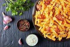 L'australiano frigge con bacon soffocato in chees fusi Immagine Stock