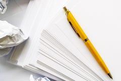 L'auteur au travail a chiffonné le stylo bille de livre blanc sur un fond blanc photo libre de droits