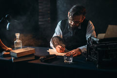 L'auteur barbu en verres écrit avec une plume Images stock