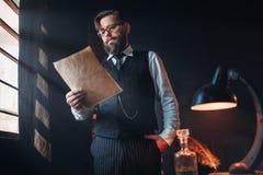 L'auteur barbu en verres lit le texte manuscrit Photos libres de droits
