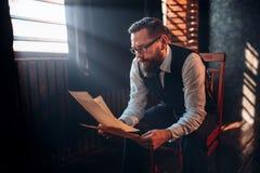 L'auteur barbu en verres lit le texte manuscrit Photographie stock