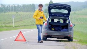 L'autista con un'automobile rotta chiamata il supporto ed ha messo le luci di rischio nel tronco video d archivio