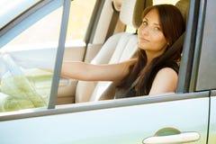 L'autista della donna passa il volante della tenuta di un'automobile Fotografie Stock