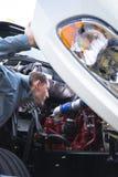 L'autista di camion dei semi ispeziona il motore funzionante di grande impianto di perforazione bianco Fotografia Stock Libera da Diritti