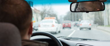 L'autista osserva la strada di città del volante di guida di veicoli dentro Immagine Stock Libera da Diritti