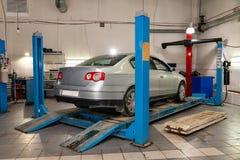 L'auto usata d'argento sta sulla convergenza di allineamento di ruota del supporto dell'automobile nell'officina per la riparazio fotografie stock