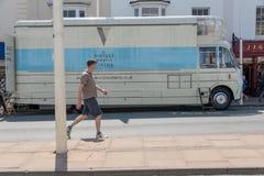 L'autobus mobile de cinéma de vintage s'est garé par le bord de la route avec des boutiques à l'arrière-plan images libres de droits