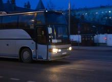 L'autobus se déplace sur la rue sombre de ville la nuit Photos stock