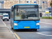 L'autobus va le long de la rue Photographie stock libre de droits