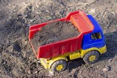 L'autocarro con cassone ribaltabile del giocattolo sta sulla terra piena della sabbia immagini stock libere da diritti