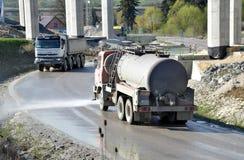 L'autocisterna dell'acqua spruzza l'acqua sulla strada per impedire la polvere sugli impianti Immagine Stock
