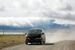 L'automobile che funziona sulla strada tibetana Fotografie Stock