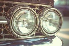 L'automobile classica con il primo piano sui fari o la lampada del faro di macera Immagine Stock