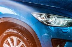 L'automobile compatta blu di SUV con lo sport e la progettazione moderna stanno lavando i wi Fotografia Stock