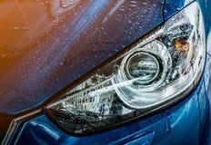 L'automobile compatta blu di SUV con lo sport e la progettazione moderna stanno lavando i wi Immagini Stock Libere da Diritti