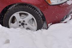 L'automobile con l'inverno si stanca sulla strada innevata Fotografia Stock