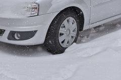 L'automobile con l'inverno si stanca sulla strada innevata Fotografie Stock Libere da Diritti